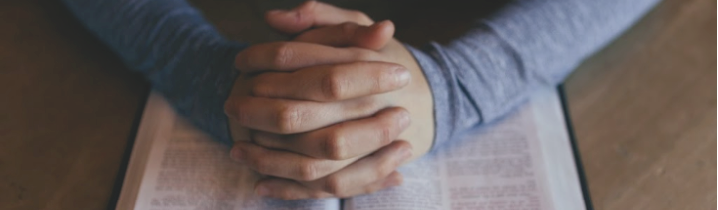folded hands praying over a bible